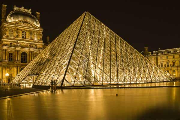 La pyramide du Louvre la nuit avec le passage richelieu en arrière plan