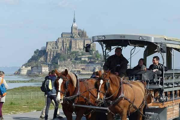 Le mont saint-michel en arrière plan et une calèche emmenant des touristes au premier plan